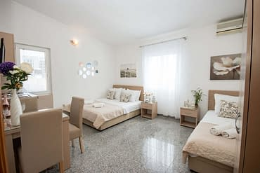 Triple studio apartment with a sea view, double and single bed, and nightstands in Villa Kovacevic
